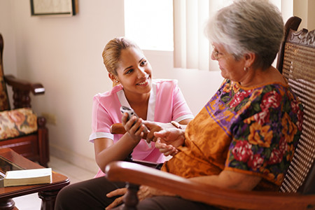 Caregiver Helping Woman With Her Medicine
