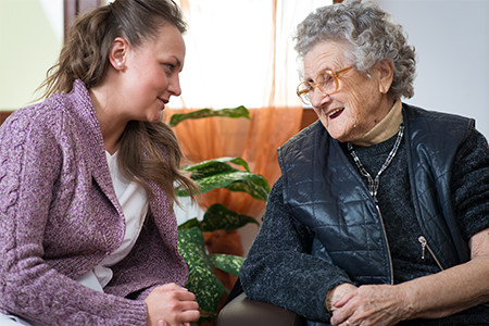 Elder Woman Receiving In-Home Care Through Her Young Caregiver