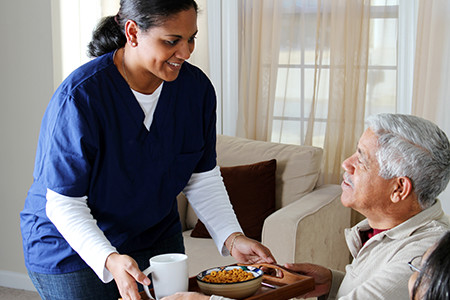 Registered Nurse Handing Food Tray To Elderly Man