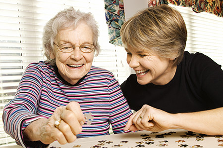 Elderly Lady getting taken care of by women while putting a puzzle together