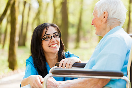Elderly man in wheel chair being taken care of by caregiver