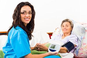 Registered-nurse-taking-blood-pressure-for-senior-in-home-care