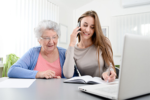 woman-helping-make-phone-call-for-elderly-lady