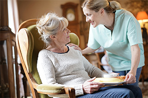 woman-receiving-her-meal-from-caregiver